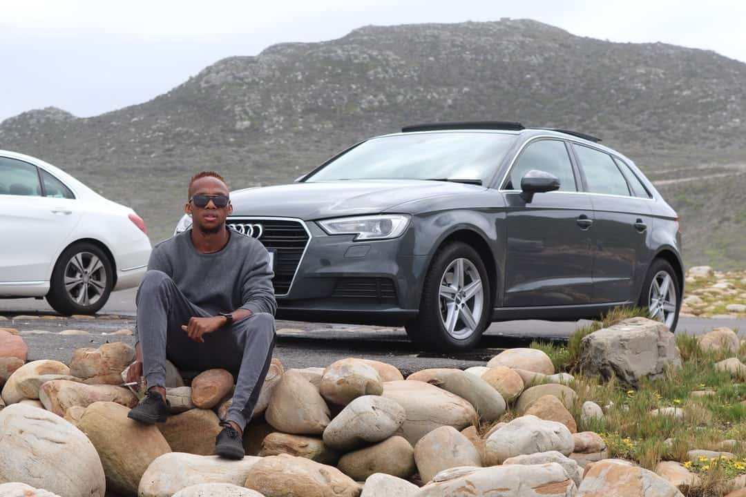 A man sitting on a rock next to a car