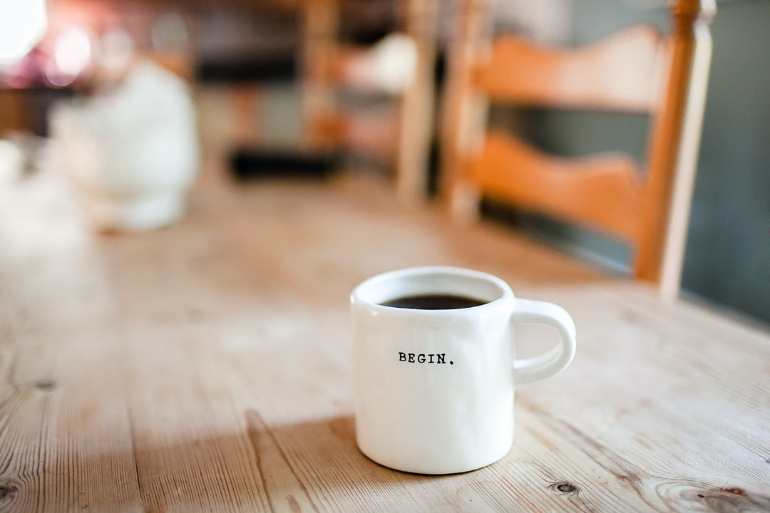 A close up of a coffee cup sitting on top of a wooden table